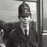 A London policeman on duty in front of a shop window