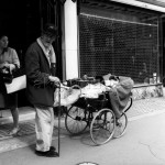 An elderly man carrying a dog and a record-player on a pram