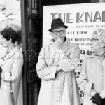 Three British citizens waiting in front of the poster of the film 'The Knack ...and How to Get It'