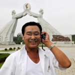 Man with mobile phone at the Monument to the Three Charters for National Reunification, 2009: © Alain Noguès / akg-images
