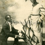 2-M191-T1-1910-1 - An elegantly-dressed black man kneeling in front of another man dressed in women's clothing, France, undated, © akg-images / Peter Weiss