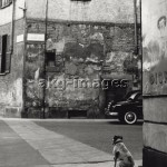 7IT-E2-AA331386 View of via Laghetto at the corner with piazza Santo Stefano. A small dog is sat down on the side of the road. Milan, the '50s. © akg-images / Mondadori Portfolio