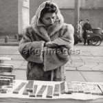 7IT-E2-AA331407 A hawker selling nougats is reading without much attention a book at her stall at the Sant'Ambrogio Fair. Milan, the '50s. © akg-images / Mondadori Portfolio