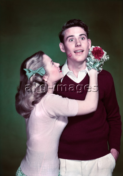 7US-C1-OC140233 ORIGINAL: 1940s 1950s TEEN COUPLE GIRL HOLDING NOSEGAY BOUQUET HUGGING SURPRISED BOY LIPSTICK KISS ON CHEEK © CAMERIQUE / ClassicStock / akg-images