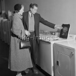 7US-C1-S5985   ORIGINAL:  1950s YOUNG COUPLE MAN WOMAN SHOPPING FOR WASHING MACHINE  © H. ARMSTRONG ROBERTS / ClassicStock / akg-images