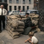7IT-E2-1297720 - A child plays near a road block at a crossroad. Belfast (Northern Ireland), July 1970 (Sergio del Grande) © akg-images / Mondadori Portfolio