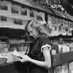 2-L45-H1-1955   Young woman at a book stall in Paris, c. 1955.  © akg-images / Paul Almasy