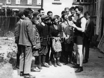 2-S70-B1-1920-5 Boy McCormick before the heavyweight championship of Great Britain in Covent Garden in London: McCormick at his training camp in Farnham surrounded by young fans © akg-images