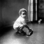 Young boy playing with a toy car, 1960sPhoto: akg-images / Paul Almasy
