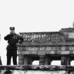 5-B1-D1-1990-59 Soldiers from the GDR border troops standing on the Wall at the Brandenburg Gate; in the background, graffiti on the Gate, 'Vive l'Anarchie,' painted on New Year's Eve, 1 January 1990. © akg-images / Günther Schaefer
