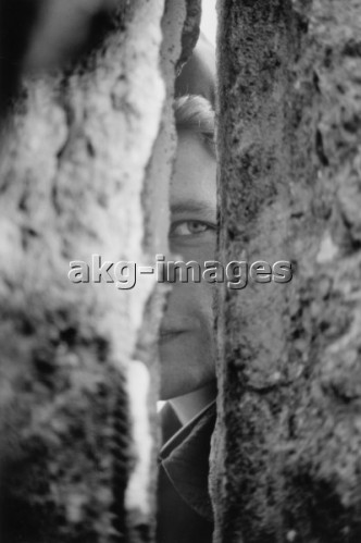 5-B1-J5-1989-36 East German border soldier looks through a crack in the Wall (after the opening of the border, 9/10 November 1989 © akg-images / Günther Schaefer