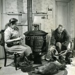 2-M141-A1-1948-1  Grandparents sitting next by the stove with their grandchild and a dog (New England, USA). - Photo, c.1948 © akg-images