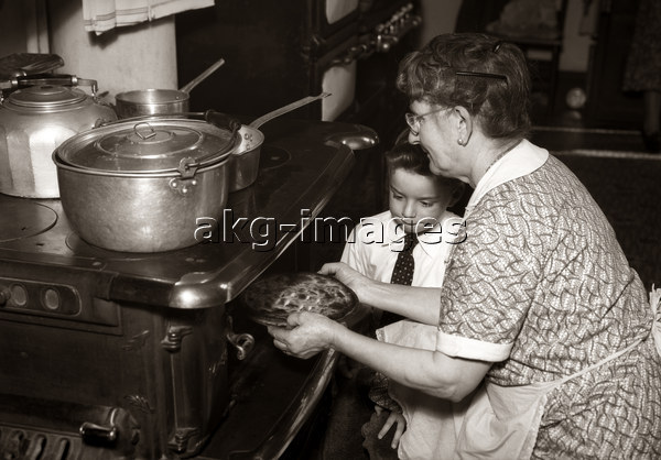 7US-C1-EG121637 BOY WATCHING GRANDMOTHER TAKING PIE OUT OF OVEN © Ewing Galloway / ClassicStock / akg-images