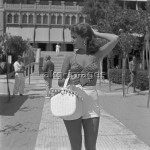 7IT-A1-0008005 American actress and singer Abbe Lane, wearing a swimming bra and a high-waisted hot pants, holding a handbag and sunglesses, portrayed standing on the path of the Excelsior Hotel, Lido, Venice 1954. © akg-images / Archivio Cameraphoto Epoche