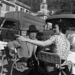 7IT-A1-0015001 American actress Ava Gardner with Humphrey Bogart sitting in front of some vans in Portofino, she is wearing a polka-dotted dress, 1954.  © akg-images / Archivio Cameraphoto Epoche