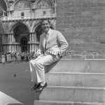 7IT-A1-0019004 Italian actor Alberto Sordi, wearing a suit, portrayed while sitting on a corner of the bell tower in St. Mark Square, smoking a cigarette, Venice, 1959.  © akg-images / Archivio Cameraphoto Epoche