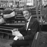 7IT-A1-0023006 American actor Burt Lancaster, wearing a tuxedo and a bow tie and reading a letter, sitting on a gondola stationary among other gondolas, Venice 1962.  © akg-images / Archivio Cameraphoto Epoche