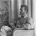 7IT-A1-0047018 Kirk Douglas portrayed from the side while sitting on a chair, wearing a vichy shirt, his fingers crossed, Venice, 1953. © akg-images / Archivio Cameraphoto Epoche