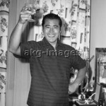7IT-A1-0058001 Japanese actor Toshiro Mifune wearing a striped t-shirt and underpants, toasting with a champagne glass, with flowered curtains behind him, in his hotel room, Venice, September 1961. © akg-images / Archivio Cameraphoto Epoche
