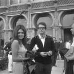 7IT-A1-0076004 Warren Beatty, wearing a cardigan and glasses, portrayed outside the Excelsior Hotel while standing next to a woman holding a newspaper, Lido, Venice 1965.  © akg-images / Archivio Cameraphoto Epoche