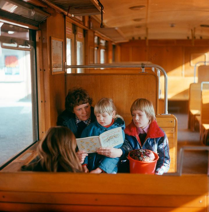 "A family in an S-Bahn carriage reads a German translation of the book ""The Story of Ferdinand"" by Munro Leaf.  Photo, Berlin (Germany) 1 February 1975 (Morgenstern) © akg-images / DDR Bildarchiv"