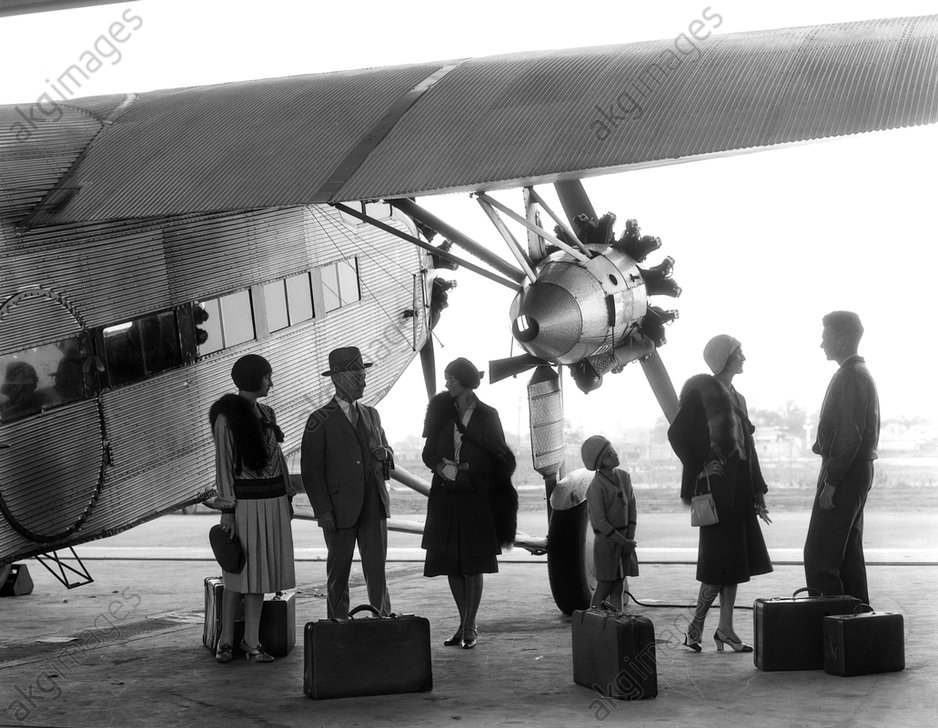 A group of passengers standing under the wing of a Ford Tri-Motor airplane, 1930s © ClassicStock / akg-images / H. Armstrong Roberts