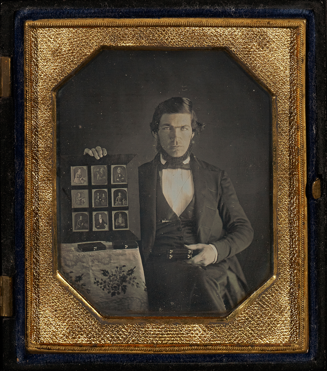 Portraits, Portraits of Men. Man holding up a selection of  daguerreotypes in a folder. Daguerreotype, USA, 1845, hand-colored; 1/6 plate, image: 6.7 × 5.2 cm.